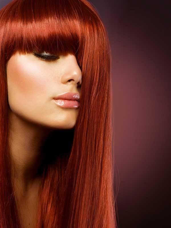 Yüzünün yarısı saçlarıyla kapanmış dolgun dudaklı kızıl saçlı kadın